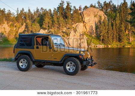 Black Hills, South Dakota - June12, 2014:   A 2003 Inca Gold Jeep Rubicon Parked Next To A Lake With