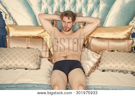 Man In Underpants Relaxing On Bed Luxury Bedroom. Man Sexy Handsome Lover Wait For You. Luxury Relax