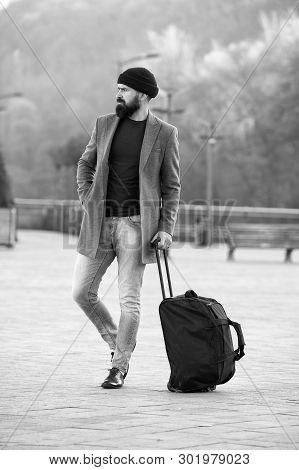 poster of Ready to travel. Carry travel bag. Business trip. Man bearded hipster travel with big luggage bag on wheels. Let travel begin. Traveler with suitcase waiting transportation to airport railway station.