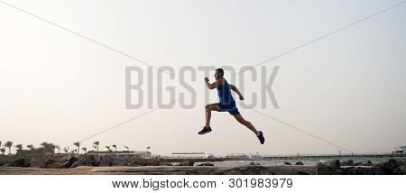 Run Hard Or Walk Home. Running Man On Beach. Runner Training Outdoors. Fit Male Sport Fitness Exerci
