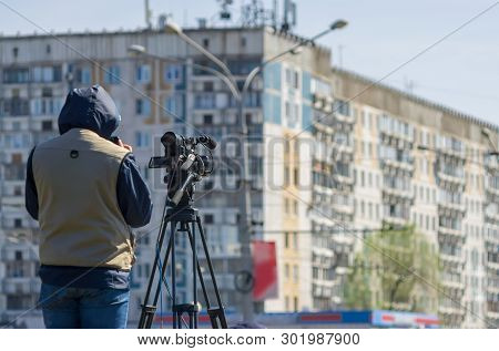 Reporter, Cameraman News Agency On A Professional Camera Shoots A Report In The City