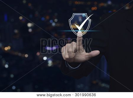 Businessman Pressing Security Shield With Check Mark Icon Over Blur Colorful Night Light City Tower