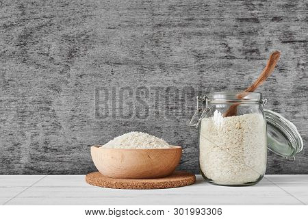 Rice Grains In Wooden Bowl And Glass Jar On Gray Background