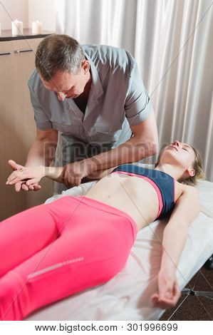 Male Manual Visceral Therapist Masseur Treats A Young Female Patient. Work With The Subconscious To