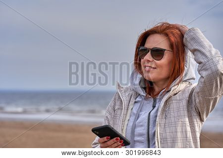 Portrait Of A Red-haired Middle-aged Woman In Sunglasses And A Raincoat Looking At A Smartphone. Sun