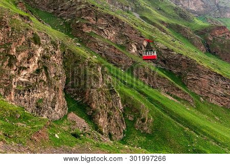 Ropeway In Caucasus Mountains. Red Cable Car Moves Down Iron Cable. Beautiful Mountain Landscape Of