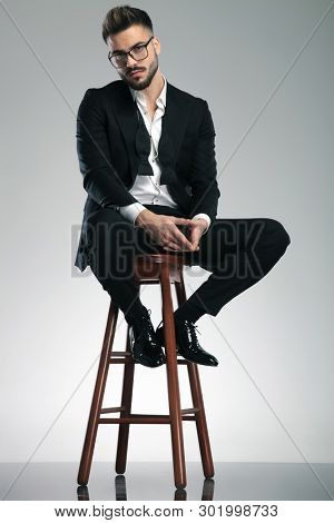 Guilty looking man sitting on a stool and playing with his fingers while wearing glasses and a black tuxedo on gray studio background