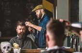 Hipster bearded client getting hairstyle. Barber with hairdryer works on hairstyle for bearded man, barbershop background. Styling concept. Barber with hairdryer drying and styling hair of client poster