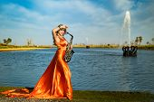 Girl with sax smiles, flirts. Happy blonde woman with big bust plays, performs on goldy saxophone in beautiful dress poster
