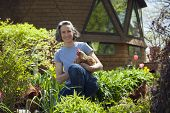 Woman at home with her chickens in her garden poster