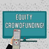 Word writing text Equity Crowdfunding. Business concept for raising capital used by startups and earlystage company Hand Holding Computer Remote Control infront of Blank Wide Color PC Screen. poster