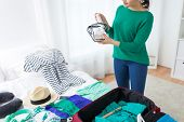 tourism, travel and luggage concept - happy young woman packing cosmetic bag with toiletries at home or hotel room poster