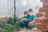 Children in an abandoned house, two poor abandoned boys, orphans as a result of natural disasters and military actions. Submission photo. poster
