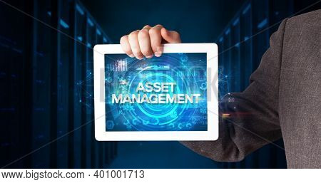 Young business person working on tablet and shows the inscription: ASSET MANAGEMENT, business concept