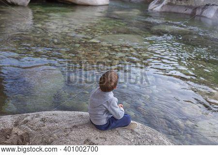 Little Boy Sitting At Clear Mountain Riverside. Enjoying Nature For Children Concept
