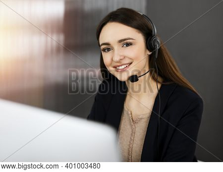 Young Friendly Girl In Headsets Is Talking To A Firms Client, While Sitting At The Desk In Sunny Off