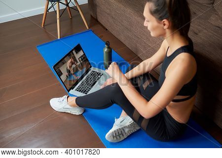 A Laptop Screen View Over A Woman's Shoulder. A Fit Girl In A Tight Suit Is Watching A Workout Video