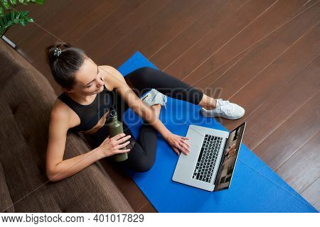 A Photo From Above Of A Sporty Girl In A Tight Suit Who Is Watching A Workout Video On A Laptop In H