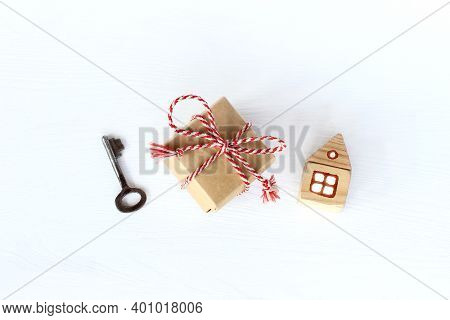 Gift With A Key And A House On A Light Surface Top View. Accommodation During The Holidays