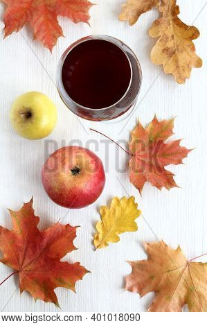 Wine In A Glass And Two Apples On A Table With Maple And Oak Leaves Top View. Autumn Still Life