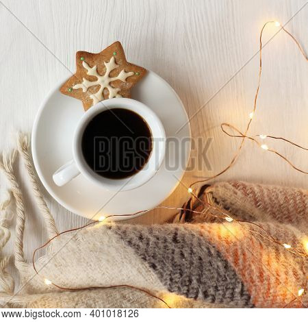 Black Coffee In A Cup With Gingerbread Cookies On A Table With A Plaid And A Garland. Festive Atmosp