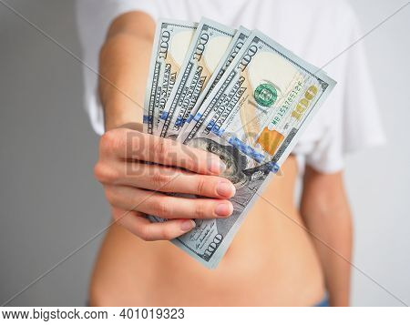In The Outstretched Female Hand, 100 Dollar Bills. The Woman Holds Out The Money. The Concept Of Wea