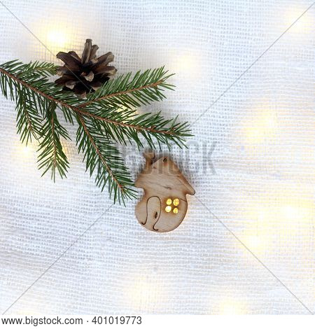 Toy House Decoration And Fir Branch With A Pine Cone On The Background Of Garland Lights. Warm Festi