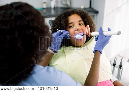 Female African Dentist Performing Dental Filling Procedure To A Little Mixed Raced School Girl In Pe
