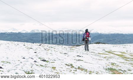 Panoramic View Of An Unrecognizable Mountaineer With A Backpack Contemplating The Snowy Landscape Of