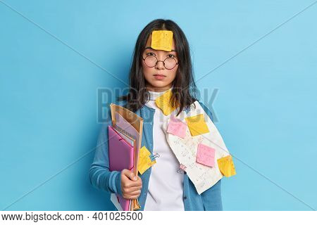 Serious Brunette Asian Woman With Sticker Stuck On Forehead Busy Doing Paperwork Prepares Financial