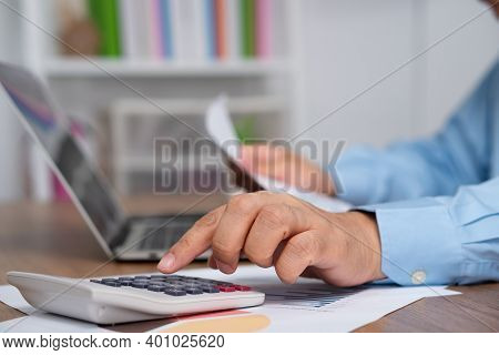 Asian Business Man Use A Calculator To Calculate Income And Expenses For Profit And Loss For Annual