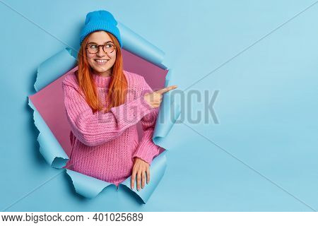 Pretty Smiling Redhead Woman In Blue Hat And Knitted Sweater Points Away On Blank Space Advertises P