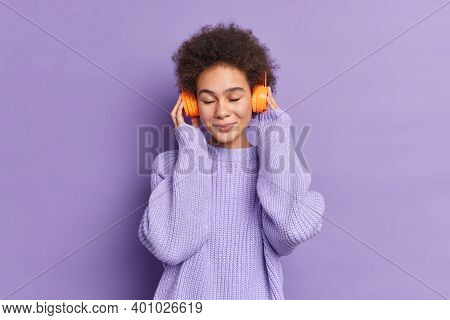 Photo Of Relaxed Teenage Girl Listens Pleasant Music Via Wireless Headphones Enjoys Every Bit Of Son