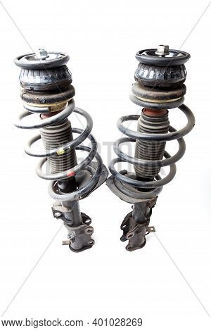 Two Shock Absorber Struts With Black Springs After Being Used On A Car During Replacement And Repair