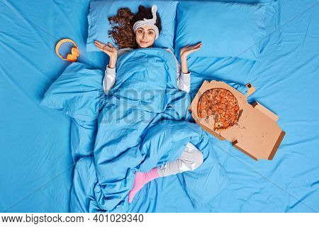 Hesitant Brunette Young Woman Shrugs Shoulders Under Blue Blanket Feels Confused Surrounded With Piz