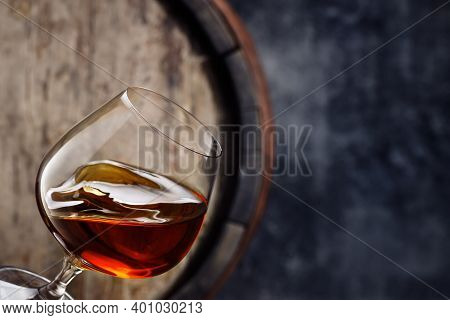 Glass Of Brandy With Wave Surface Level And Old Wooden Barrel As Background