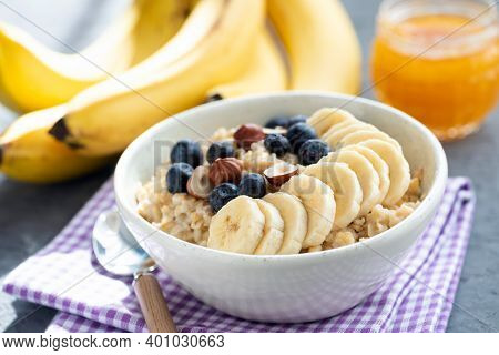 Healthy Breakfast Oatmeal Bowl With Fruits And Nuts On A Purple Table Napkin. Vegan Oatmeal With Ban