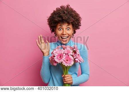 Impressed Surprised Happy African American Woman Raises Hand Dressed In Blue Turtleneck Comes To Con