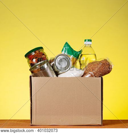 Food Donation Concept. Donation Box With Food For Donation On Yellow. Assistance To The Elderly In T