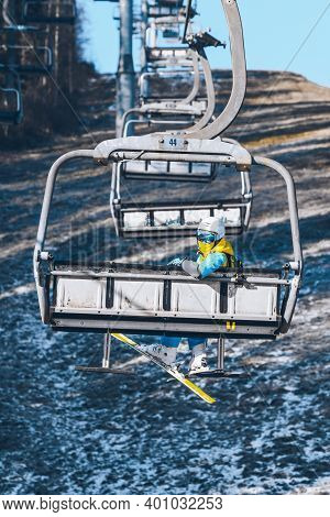 Woman Going Up By Chairlift To Ski