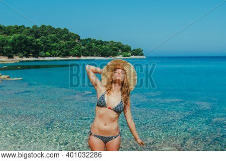 Young Pretty Woman In Swimsuit Enjoying Sunny Day Sea With Blue Clear Water On Background