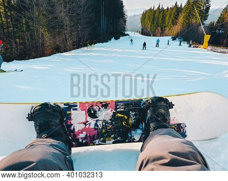 Man With Snowboard Sitting On Skiing Slope
