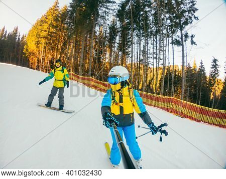Couple Riding Down By Slope On Snowboard And Skies
