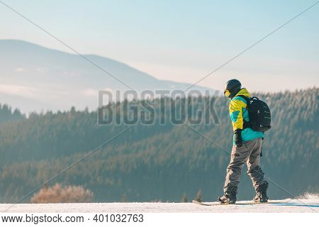 Man Snowboarding Down By Hill Mountains On Background