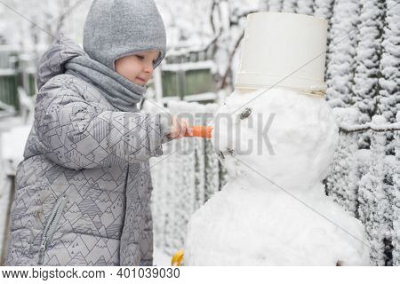Boy Makes A Snowman. Adorable Kid Boy Making A Snowman, Playing And Having Fun With Snow, Outdoors O