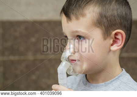 Child Holds A Mask Vapor Inhaler. Child Who Got Sick By A Chest Infection After A Cold Or The Flu Th