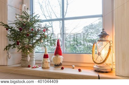Christmas Lantern, Christmas Gnome, Christmas Tree And Red Decor On The Window Of A Wooden House Ove
