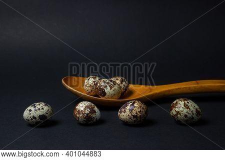 Quail Eggs On A Black Background. Healthy Food. Quail Eggs Lie In A Wooden Spoon, Several Eggs Lie S