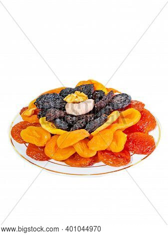 A Set Of Dried Fruits On A Plate. Dried Apricots, Prunes, Figs. Isolate