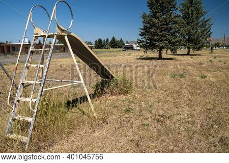 Cokeville, Wyoming - August 6, 2020: Swingset And Playground At An Old Abandoned Seedy Motel, With O